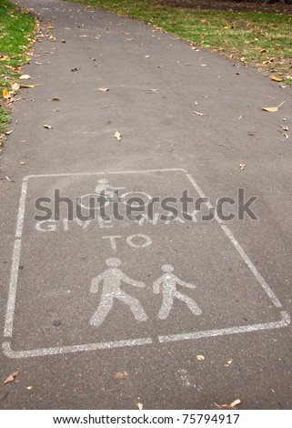 Sign on pedestrian path requesting cyclists to give way. - stock photo