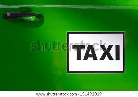 Sign On The Door Of A Bright Green Taxi - stock photo