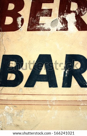 Sign on yellowish old wall with letters saying bar - stock photo