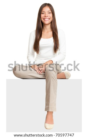 Sign people. Woman sitting on blank billboard placard sign. Casual young beautiful multiracial Asian isolated on white background. - stock photo