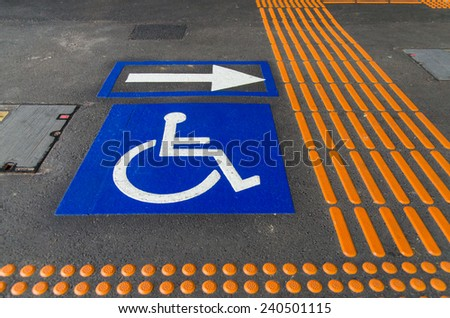 Sign pointing wheelchair users towards the lift at a railway station, with tactile paving to guide vision impaired persons.