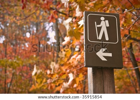 Sign points to a hiking trail in woods in autumn