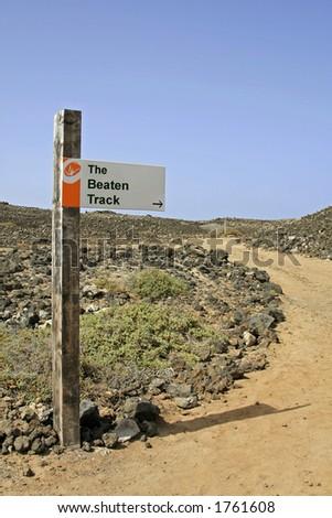 Sign post - The Beaten Track - stock photo