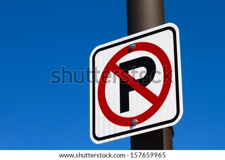 Sign showing a capital P with a red circle denoting a no parking area is attached to a pole against a blue sky. - stock photo