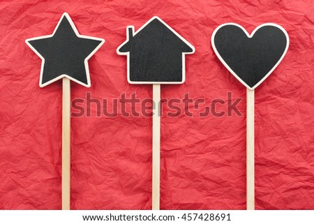 Sign, star, house, heart lie on the red crumpled paper, with place for your text