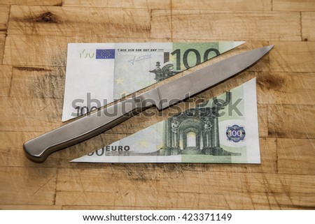 Sign, symbol, idea , concept of Money divide - cutting one whole bill 100 euro with the knife Two half Objects lie on wooden kitchen board Natural material texture - stock photo