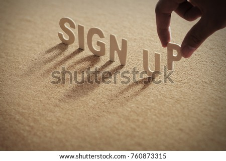 SIGN UP wood word on compressed or corkboard with human's finger at P letter.