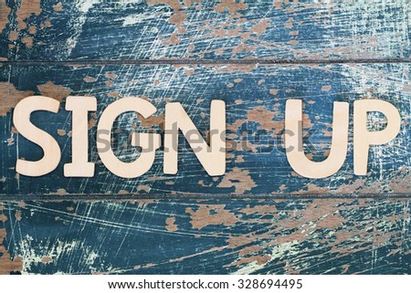 Sign up written with wooden letters on rustic surface