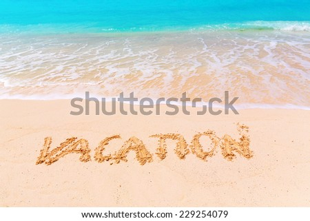 Sign VACATION on the beach with turquoise water, Zanzibar, Tanzania - stock photo