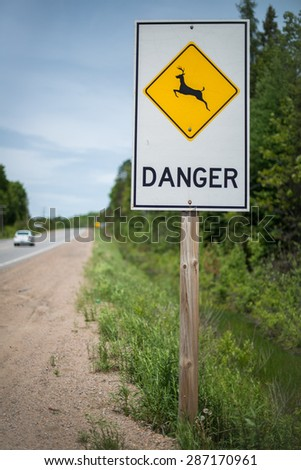 Sign warning motorists of danger from crossing animals - stock photo