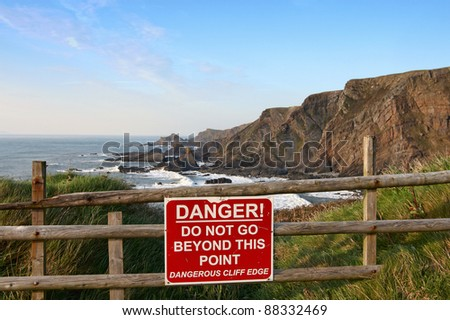 Sign warning of danger at cliff edge - stock photo
