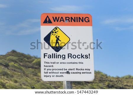 Sign warning of the danger of falling rocks along a hiking trail - stock photo