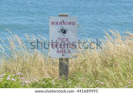 "Sign ""Warning, tick infested area"" on Long Island (USA) seashore - stock photo"