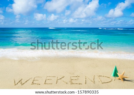 "Sign ""Weekend"" on the sandy beach by the ocean"