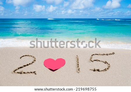 "Sign ""2015"" with heart on the sandy beach by ocean"