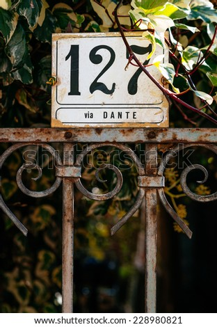 Sign with house number 127 on the fence in Italy - stock photo
