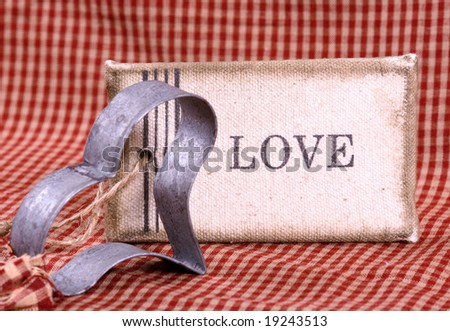 Sign with the word love on it with a heart shaped metal cookie cutter - stock photo