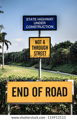 Signage indicating the end of the road and implications of road expansions into the jungle