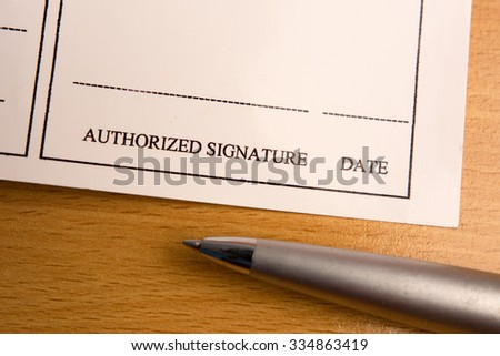 Signature field on business document with pen on wooden table
