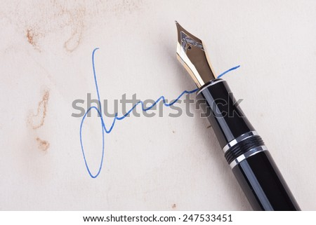 Signature on old paper with old fountain pen - stock photo