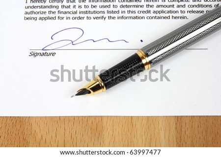 Signature under a business contract agreement with a fountain pen. - stock photo
