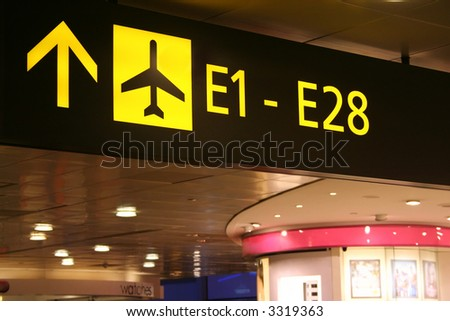 Signboard at the airport showing directions to the boarding gates. - stock photo