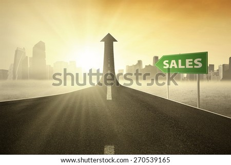 Signboard on the street with a Sales text pointing at a road turning into arrow upward - stock photo