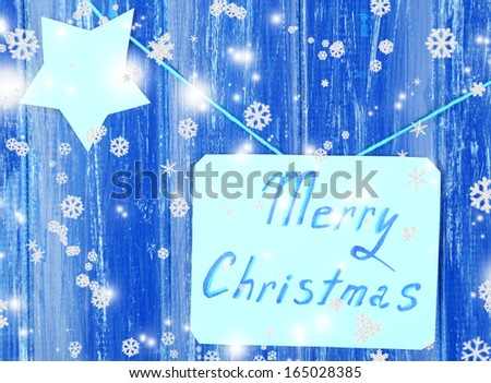 Signboard with words Merry Christmas on blue wooden table background close-up - stock photo