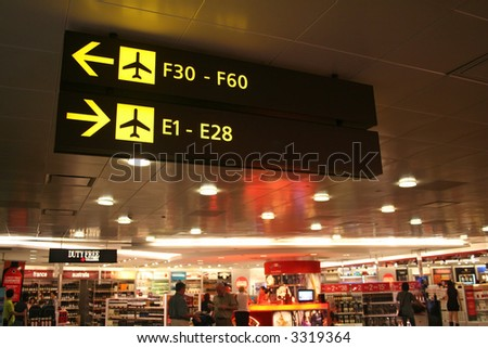 Signboards at the airport showing direction of the boarding gates while passengers shop in the background. - stock photo