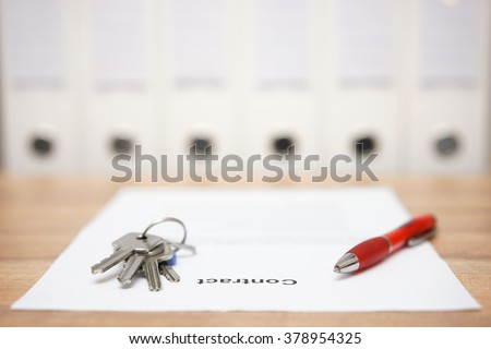 signed contract and keys of the property with documents  in background, concept of business  premise deal - stock photo