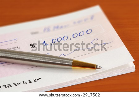 Signed one million dollars cheque and a pen - stock photo