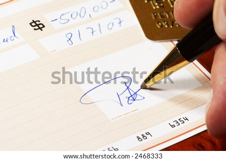 signing a bank check, gold credit card in background - stock photo