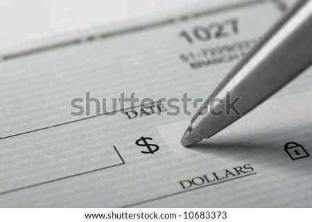 Signing a blank check with a chrome pen - stock photo