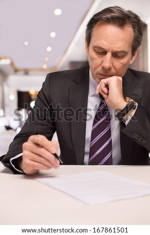 Signing a contract. Thoughtful mature man in formalwear signing a document and holding hand on chin - stock photo