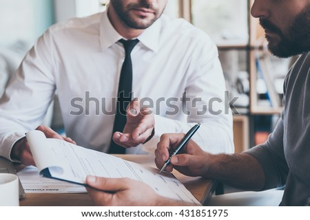 Signing contract. Close-up of confident young man signing some document while another man in shirt and tie sitting close to him and pointing document  - stock photo