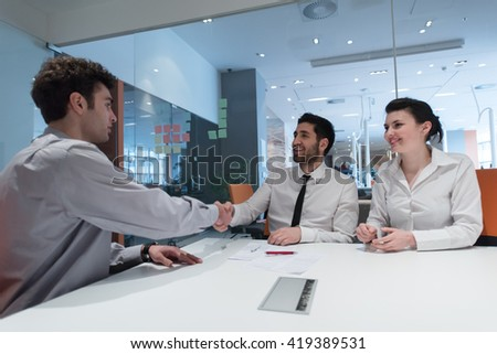signing contract on partners back, young couple on business meeting with life insurance and bank loan agent at modern office interior - stock photo