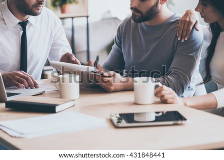 Signing documents. Close-up of confident young man signing some document while sitting together with his wife and man in shirt and tie  - stock photo
