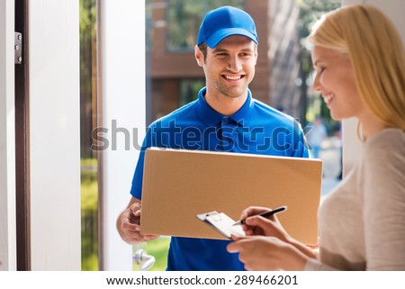 Signing for the package. Smiling young delivery man holding a cardboard box while beautiful young woman putting signature in clipboard  - stock photo