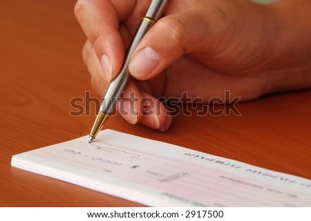 Signing money cheque - stock photo