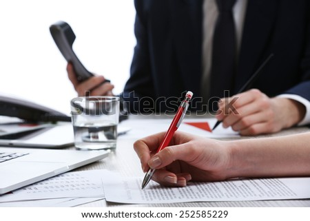 Signing of documents at worktable on white blurred background - stock photo