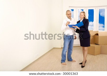 Signing of documents by the owner in an interior of new apartment - stock photo