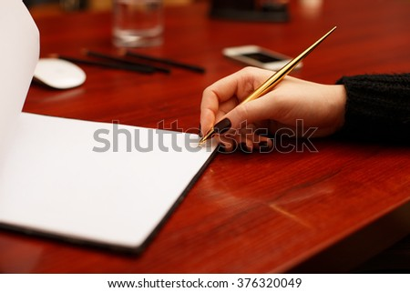 signing of documents. Hand with the pen and sheet of notepaper on a desk top.  - stock photo