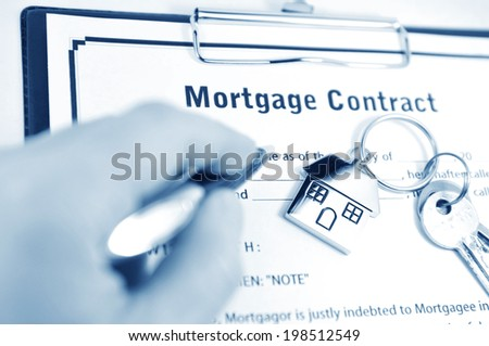 Signing the mortgage contract with keys and symbolic house keyring - stock photo