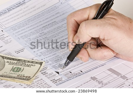 Signing your tax form and money ready to submit for payment
