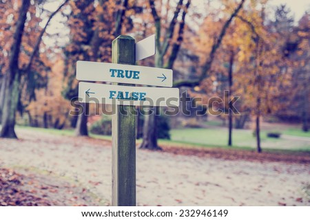 Signpost in a park or forested area with arrows pointing two opposite directions towards True and False. - stock photo