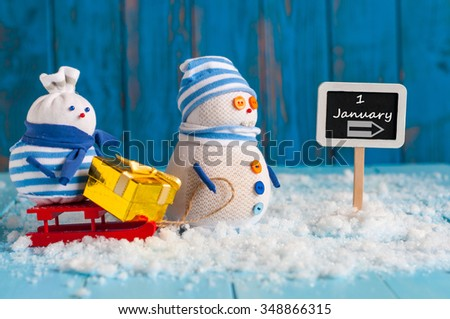 Signpost of the 1 January and two Snowman with red sled and gift stand near direction sign. Happy new year postcard. - stock photo