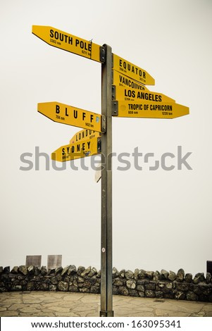 Signpost on Cape Reinga headland on the northernmost tip of the North island of New Zealand. - stock photo