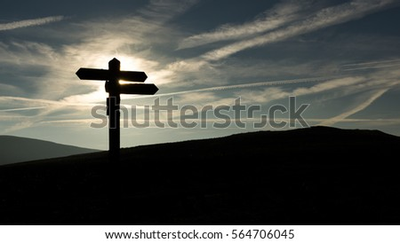 Signpost silhouetted against a cloudy blue sky in winter.