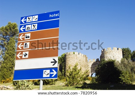 Signpost with blue, white an brown plates showing directions near a medieval castle, Portugal - stock photo