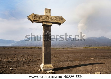 Signposts pointing to the bottom of the volcano caldera. Mt. Bromo volcano during sunrise, the magnificent view of Mt. Bromo located in Bromo Tengger Semeru National Park, East Java, Indonesia. - stock photo